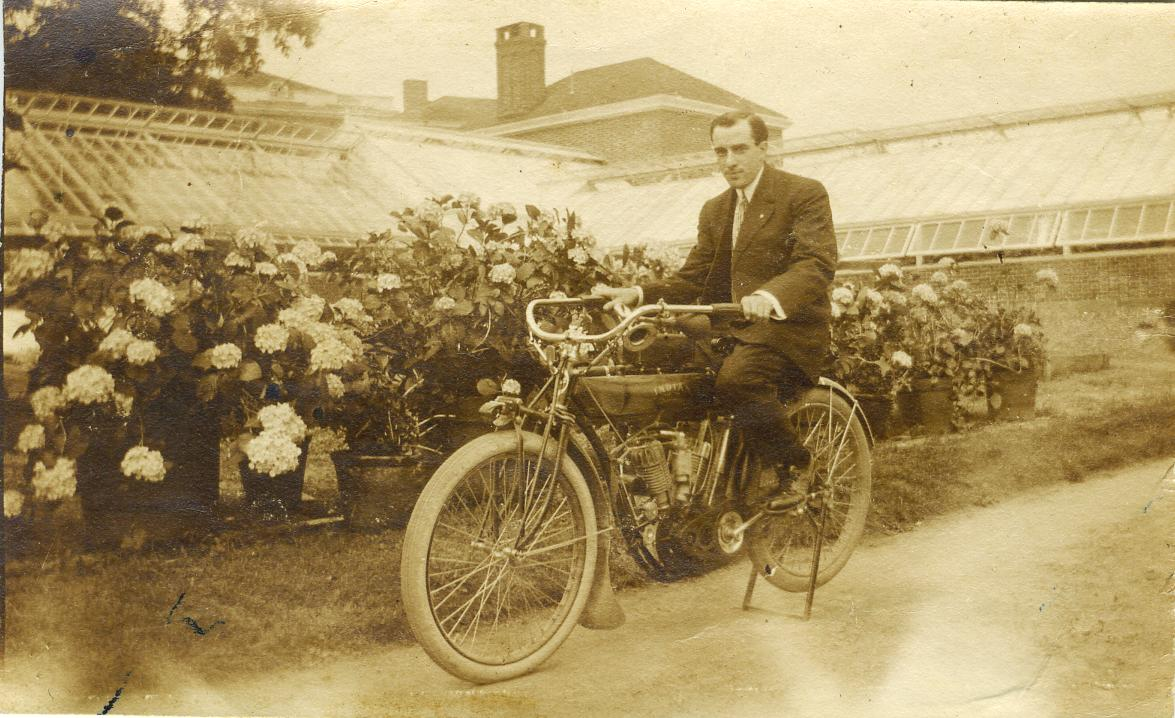 Forest Mills Rhodes on Indian motorcycle near greenhouses at Ream Estate c1908